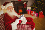 Happy santa using tablet on the couch