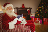 Cheerful santa using tablet on the couch