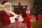 Happy santa touching tablet on the couch