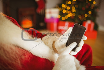 Santa claus touching a smartphone at christmas