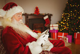 Concentrated santa using smartphone at christmas