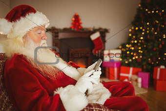 Concentrated santa using smartphone at christmas