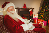 Smiling santa using smartphone at christmas