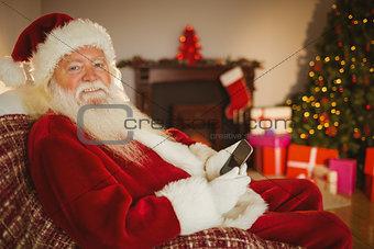 Smiling santa using smartphone at christmas