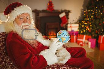Smiling santa claus holding a globe