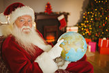 Smiling santa pointing his finger on the globe