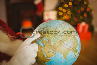 Close up of santa pointing his finger on the globe