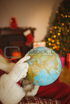 Santa pointing his finger on the globe