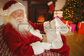 Smiling santa claus reading his list