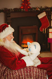 Santa claus holding piggy bank at christmas