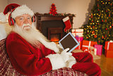 Santa claus listening music and using tablet