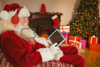 Santa listening music and touching tablet