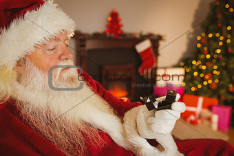Santa claus holding engagement ring with his box