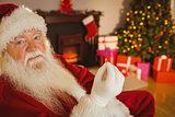 Smiling santa holding engagement ring