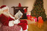 Santa claus reading newspaper on the couch