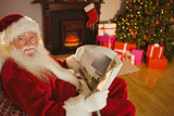 Smiling santa claus reading newspaper