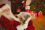Smiling santa claus reading newspaper