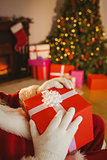 Santa claus holding a red gift with a white bow