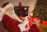 Smiling santa claus holding gift