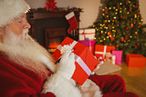 Santa claus writing on a red gift