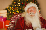 Content santa relaxing on the armchair
