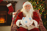 Smiling santa offering piggy bank