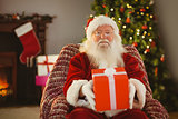 Santa claus offering a red gift