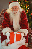 Cheerful santa claus holding present