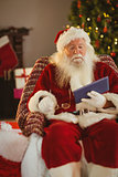 Santa holding his glasses and using tablet