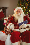 Happy santa holding glasses and tablet