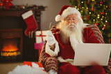 Santa claus using laptop on the armchair