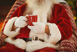 Mid section of santa holding hot drink