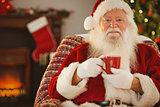 Smiling santa claus holding a mug