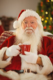 Happy santa claus holding a red mug