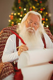 Santa claus writing list on the armchair