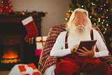 Santa claus using tablet on the armchair