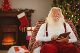 Smiling santa using tablet on the armchair