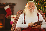 Smiling santa using digital tablet