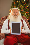 Smiling santa showing tablets screen