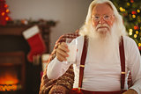 Cheerful santa holding a glass of milk