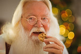 Happy santa claus eating a cookie
