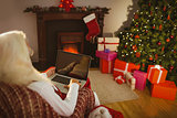 Santa sitting and using laptop on the armchair