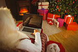 Santa sitting on the armchair and typing on laptop
