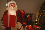 Surprised santa claus delivering a glowing gift