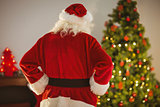 Rear view of santa standing in front of the christmas tree