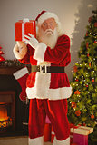 Father christmas holding gift at christmas eve