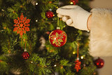 Hand of santa hanging a bauble
