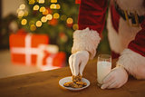 Santa picking cookie and glass of milk