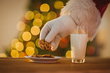Hand of santa claus picking cookie