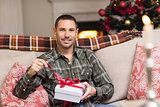 Smiling man opening a gift on christmas day